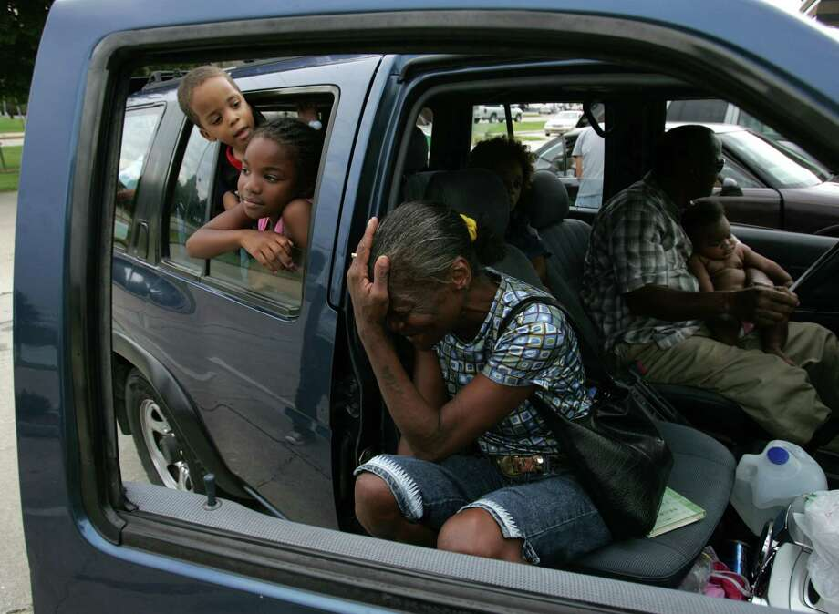Hilda Lawrence, of New Orleans, sits with her family after arriving in Baton Rouge following a six-hour drive as they evacuated. Lawrence, who was recovering from a recent surgery, and her husband, Larry, in the driver's seat, packed 10 other people in their vehicle to get out of Hurricane Katrina's path. Photo: BRETT COOMER, HOUSTON CHRONICLE / HOUSTON CHRONICLE
