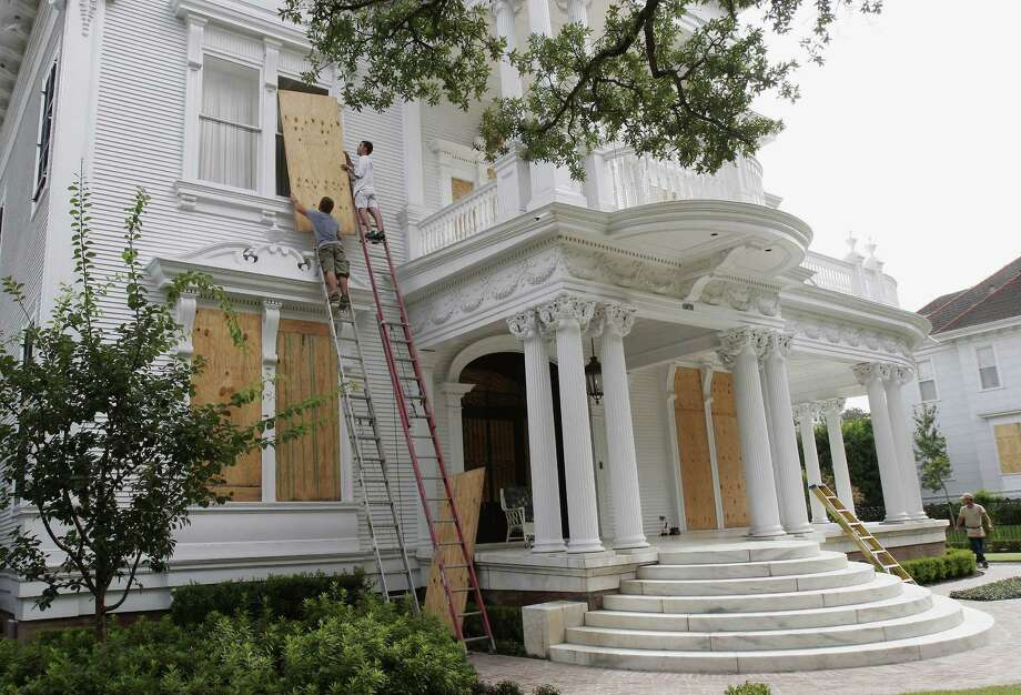 Scott Kroehle, left, and John Witherspoon board up one of the many majestic Garden District homes in New Orleans. Photo: BILL HABER, AP / AP