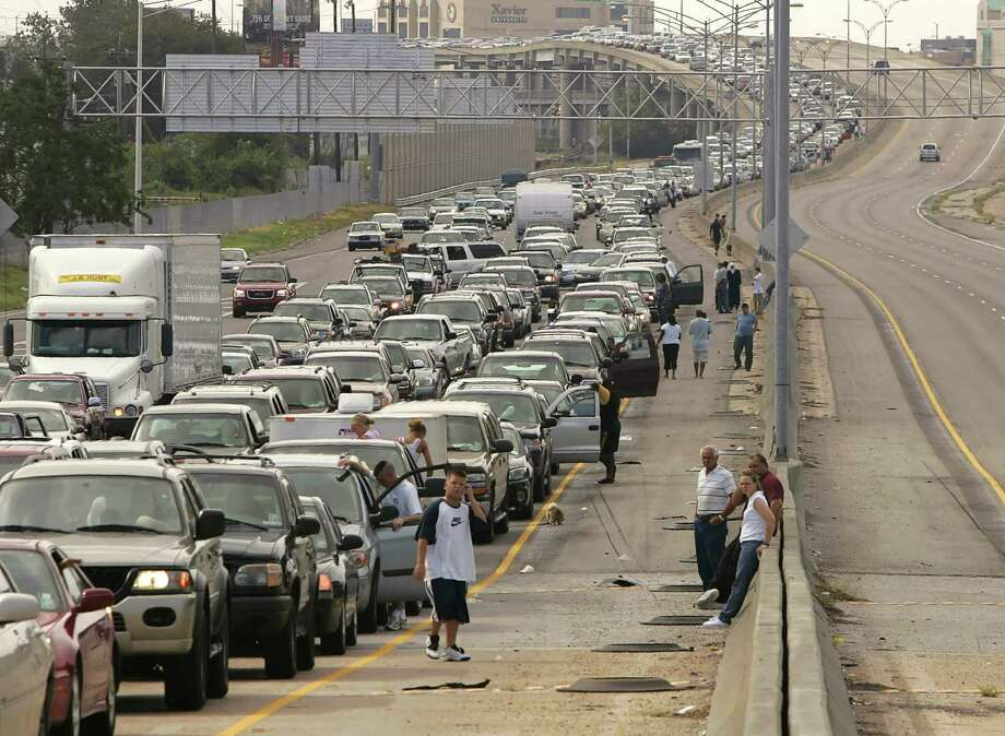 Drivers and passengers wait outside their cars as traffic snarled on the interstate highway leaving downtown New Orleans. Photo: RICK WILKING, REUTERS / X00301