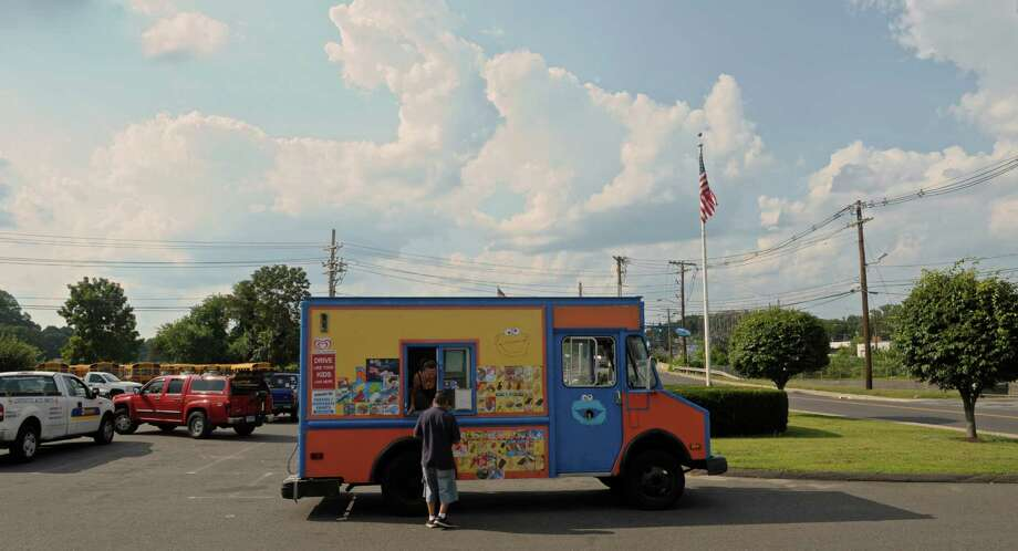 Elisabet Esposito stops one of the J&E Ice Cream trucks at a Danbury auto parts store. Photo: H John Voorhees III / Hearst Connecticut Media / The News-Times