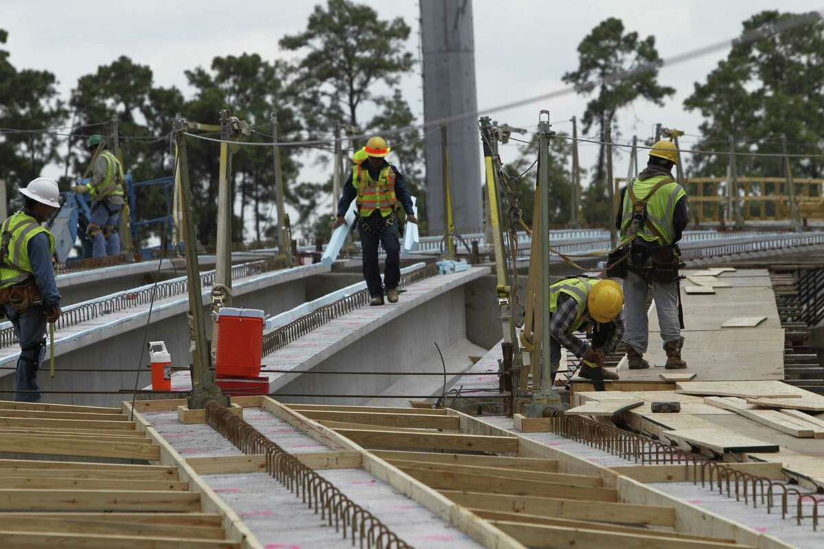 Workers work on a ramp from the Hardy Toll road Wednesday, Aug. 19, 2015, in Houston.
