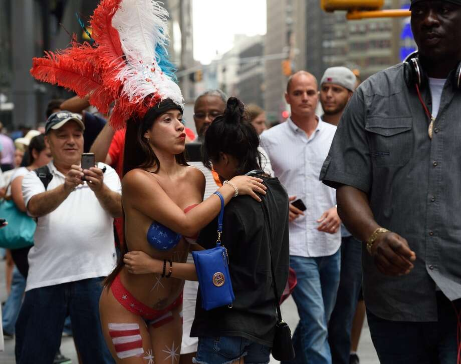The Desnudas(Warning: The rest of the photos may not be safe for work)  A young woman poses with tourists in Times Square wearing body paint to cover herself on August 19, 2015 in New York. Mayor Bill de Blasio said that he sees the desnudas in Times Square as pushy panhandlers. Photo: DON EMMERT, AFP/Getty Images