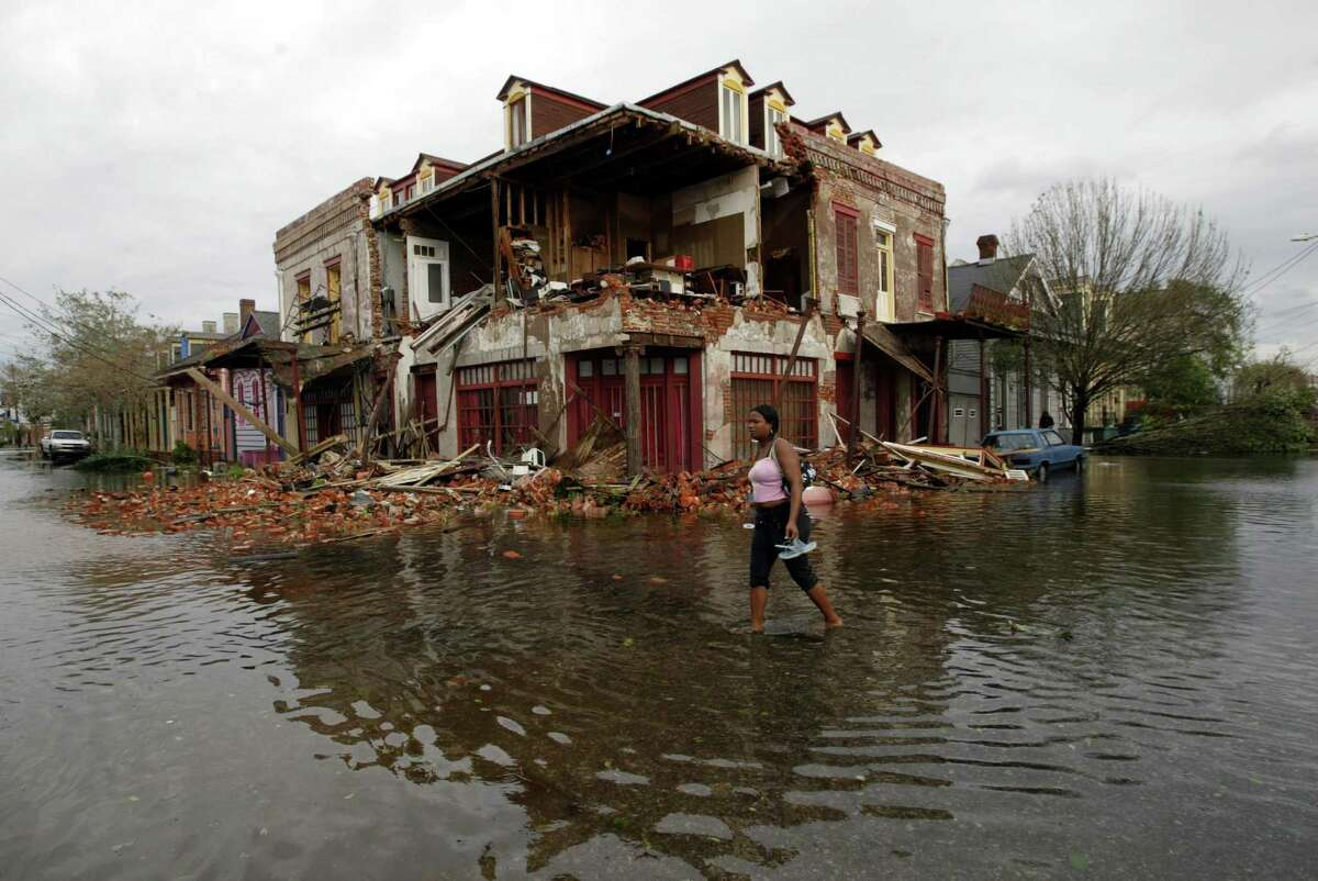 An unidentified woman walks by a home destroyed by Hurricane Katrina on the corner of Burgundy and Touro in the Historic District of New Orleans.