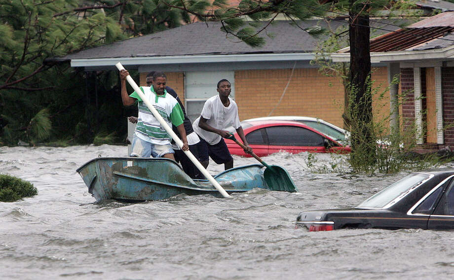 Elvin Duckworth (from left), Jonathan Harvey and Leonard Harvey paddle a row boat through a flooded street in their Gulfport, Miss., neighborhood.  Photo: JOHN BAZEMORE, AP / AP