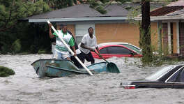 Elvin Duckworth, left, Jonathan Harvey, center, and Leonard Harvey paddle a row boat through a flooded street in their Gulfport, Miss, neighborhood after Hurricane Katrina struck the Gulf Coast Monday,  Aug. 29, 2005 .