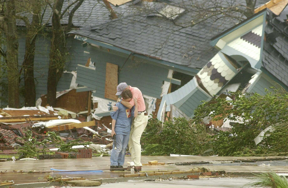 Sam Miller, 10, left, is consoled by a neighbor after viewing the destruction of his home along Beach Boulevard in Pascagoula, Miss. Photo: WILLIAM COLGIN, AP / THE MISSISSIPPI PRESS-REGISTER