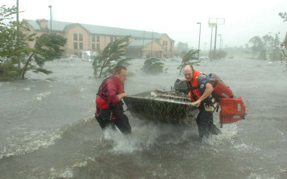Fire and rescue personnel launch a boat amid floodwaters from Hurricane Katrina, as they head out to rescue a family outside a hotel in Pascagoula, Miss. Photo: MICHAEL SPOONEYBARGER, AP / THE TAMPA TRIBUNE