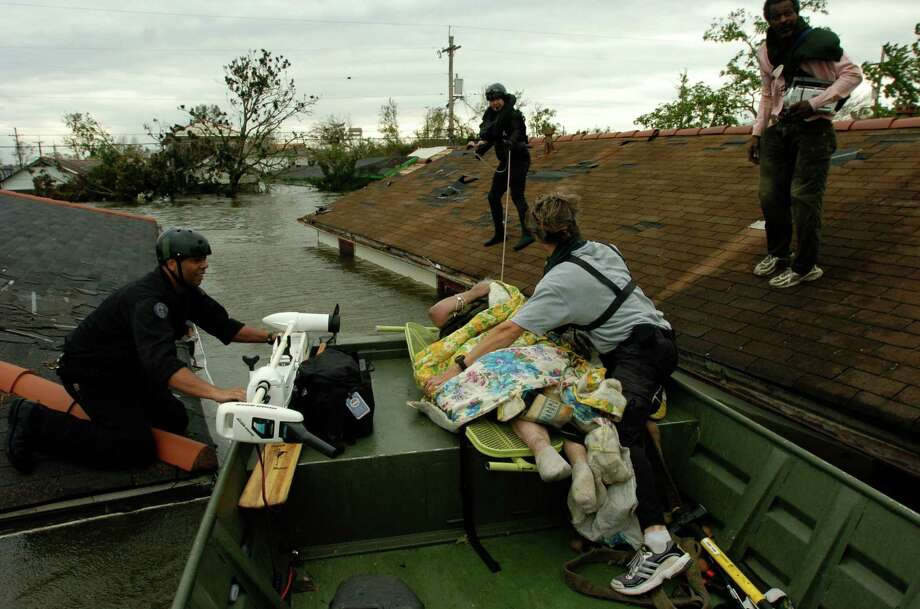 After floating to her attic on an air mattress, Lois Rice, who can't walk, is placed on a neighbor's ironing board after New Orleans police cut a hole in her roof to reach her. Photo: MELISSA PHILLIP, HOUSTON CHRONICLE / HOUSTON CHRONICLE