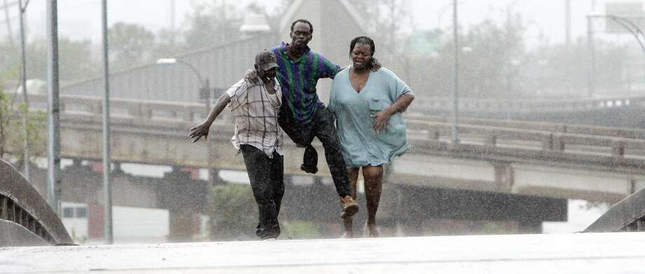 Sammuel Dunn is helped to safety by friends after he was rescued by a boat after his home flooded.  Photo: ERIC GAY, AP / AP