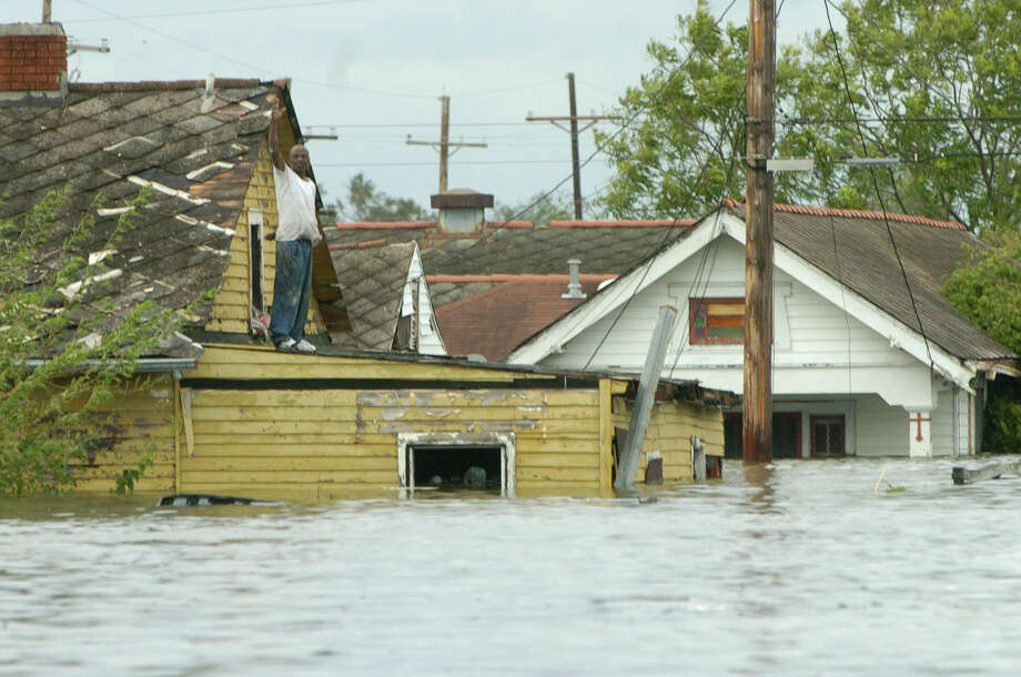 A man on his roof in the lower 9th  Ward waves to a passing NOPD Swat rescue boat. The officers had to pass up many who were stranded in order to rescue those who were in more serious and dangerous positions. Photo: MELISSA PHILLIP, HOUSTON CHRONICLE / HOUSTON CHRONICLE