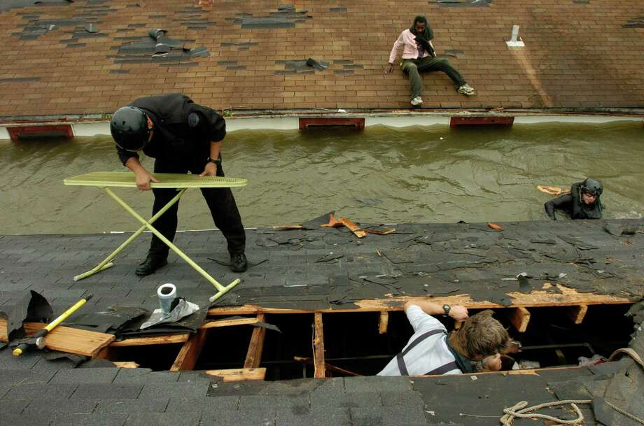 NOPD Swat officer Lt. Todd Morrel (left) tries to fold up an ironing board as Lt. Chris Mandry (right) swims back from a neighboring home as they along with  New Orleans Times Picayune photographer Alex Brandon worked to rescue Lois Rice. The officers cut a hole in the roof to rescue her from her flooded home in the lower 9th Ward. She floated on an air matress to her attic. The neighbor on next roof gave the officers an ironing board for them to use as a stretcher. She cannot walk.  Since the neighbor gave them the ironing board they took him on the boat also. Photo: MELISSA PHILLIP, HOUSTON CHRONICLE / HOUSTON CHRONICLE