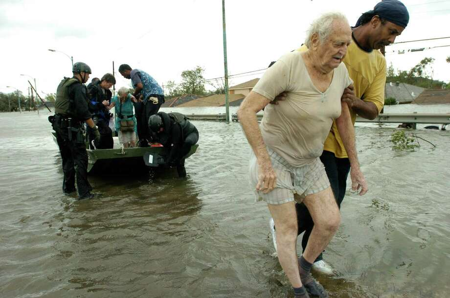 Henry Winter is helped onto shore as his wife, Heloise, prepared to exit the boat that New Orleans police officers used to rescue them when their home flooded in the Crescent City's lower 9th Ward. Photo: MELISSA PHILLIP, HOUSTON CHRONICLE / HOUSTON CHRONICLE