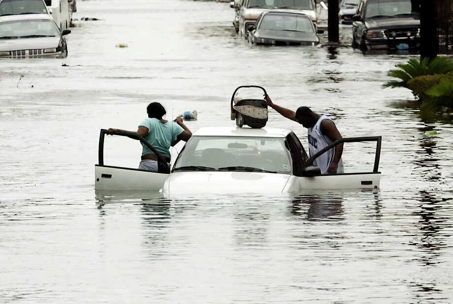 A man put his baby on top of his car as he and a woman abandoned their car after it started to float. Photo: RICK WILKING, REUTERS / X00301