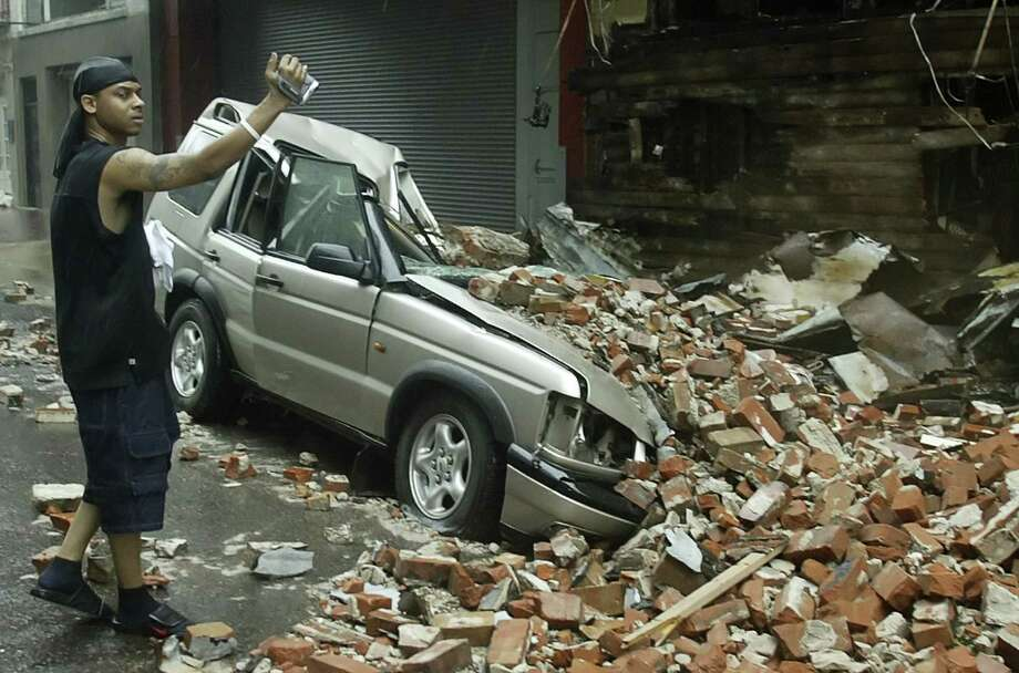 A man videotapes a car crushed after a side of a building collapsed in downtown New Orleans. Photo: RICK WILKING, REUTERS / X00301