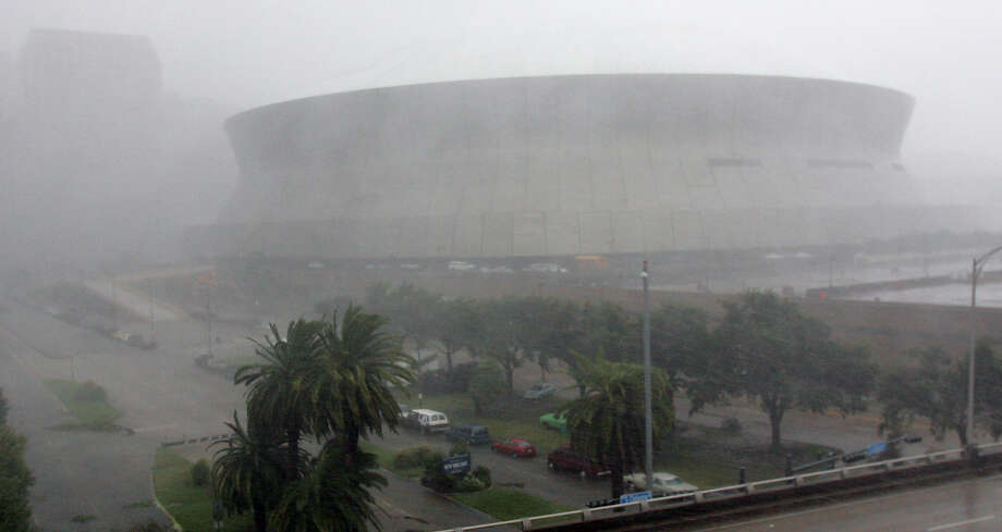 High winds and rain pounds the Louisiana Superdome. Officials reported that part of the roof of the Superdome was blown off because of the storm and the facility, which is housing some 10,000 evacuees, was leaking. Photo: DAVE MARTIN, AP / AP