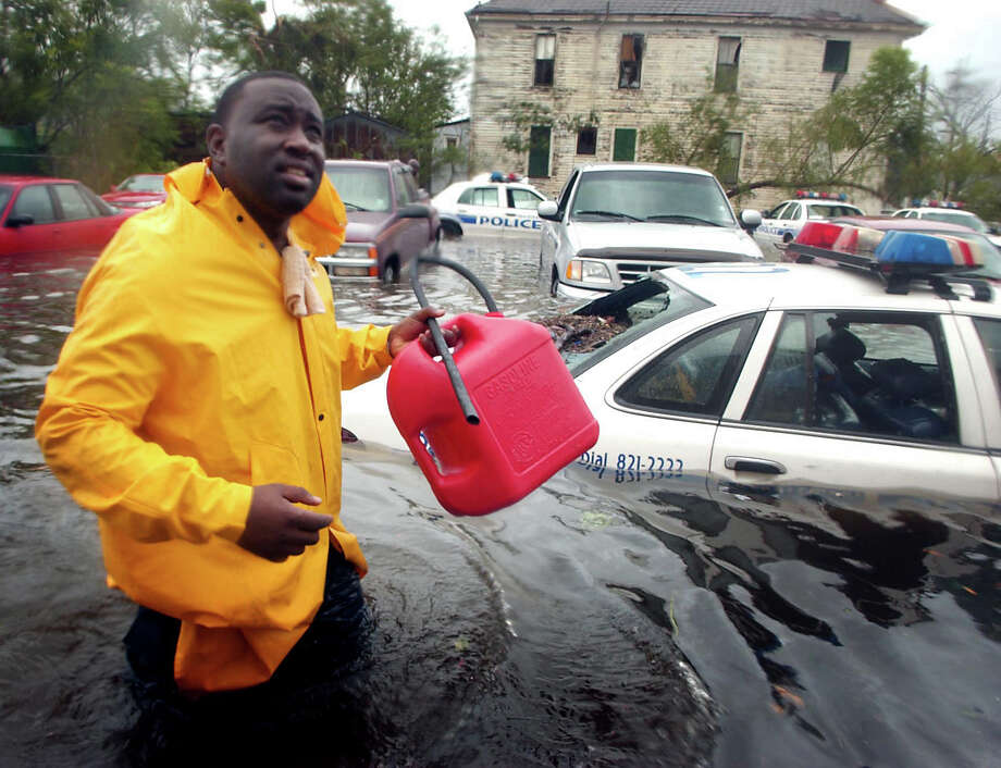 Officer N. Daggs trudges through Hurricane Katrina floodwaters to search for fuel to siphon to run generators at Bywater Hospital in New Orleans. The generators were used to power equipment for patients unable to be transported. Photo: MATT ROURKE, AP / AUSTIN AMERICAN-STATESMAN
