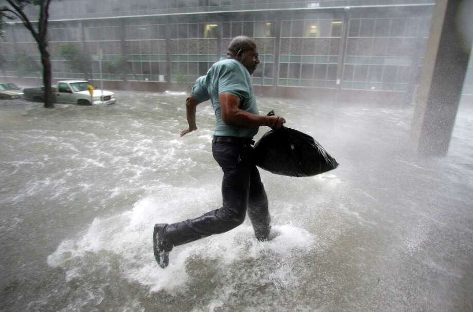 Arnold James tries to keep his footing during a strong gust while he made his way to the Louisiana Superdome.  The roof of his home blew off, forcing him to seek shelter. Photo: DAVE MARTIN, AP / AP