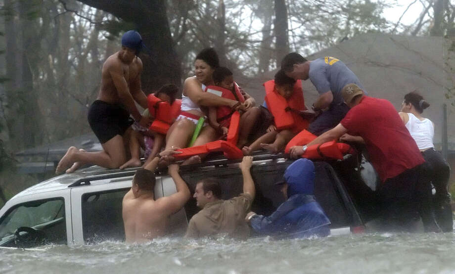 Bay St. Louis Emergency Management Agency volunteer crews rescues the Taylor family from the roof of their suburban, which became trapped on US 90 due to flooding during Hurricane Katrina in Bay St. Louis, Miss. Photo: BEN SKLAR, AP / AP