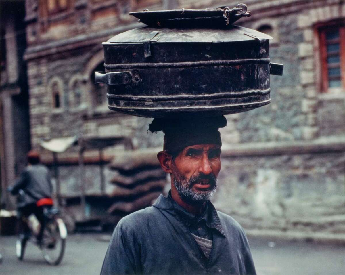 A man with containers on head walks along a road in Kashmir. It is one of the photographs on display at the Bruce Museum in Greenwich that are part of