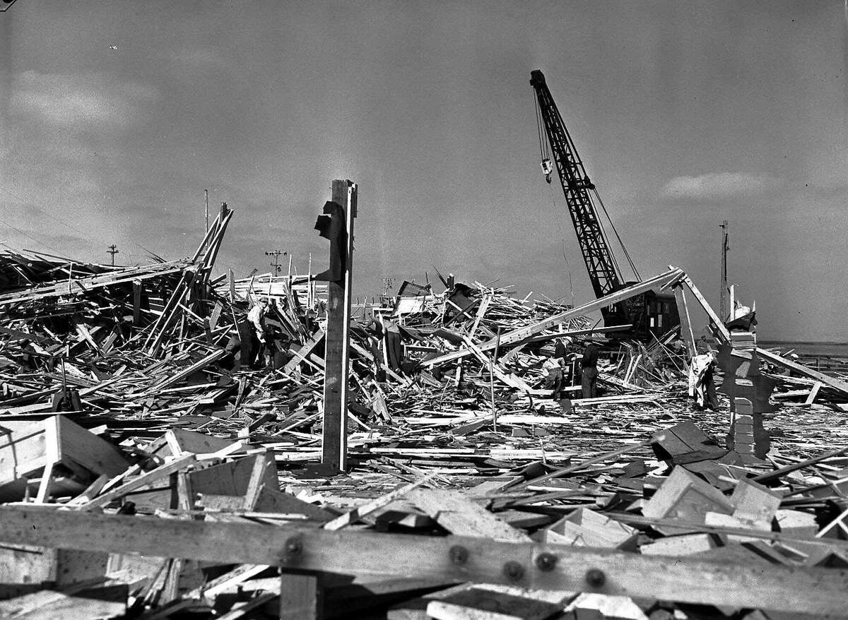 ** FILE ** In this file photo, workmen search through what was the carpenter shop on the pier at Port Chicago, Calif., after the building was leveled by the explosion of two munitions ships the evening of July 17,1944. The site of the World War II explosion that killed 320 people, over 200 of them black sailors, raised enough outrage about the treatment of the black survivors to encourage desegregation of the Armed Forces could become part of the National Park System under a new bill. (AP Photo/File) Ran on: 07-30-2007 Before the explosion, Navy workers loaded ammunition into a ship's cargo net at Port Chicago.