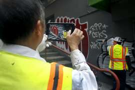 Yu Cheng (left) and Lorenzo Soriano of the Department of Public Works photographs graffiti on a building in Chinatown's Vinton Alley before covering it with a fresh coat of paint in San Francisco, Calif. on Friday, Aug. 21, 2015. The crew uploads the photographs to the city's 311 website where they will be collected and used for possible legal action. The city attorney's office is suing a serial tagger known as Cozy Terry and is seeking more than $50,000 in damages for repeatedly defacing city property.