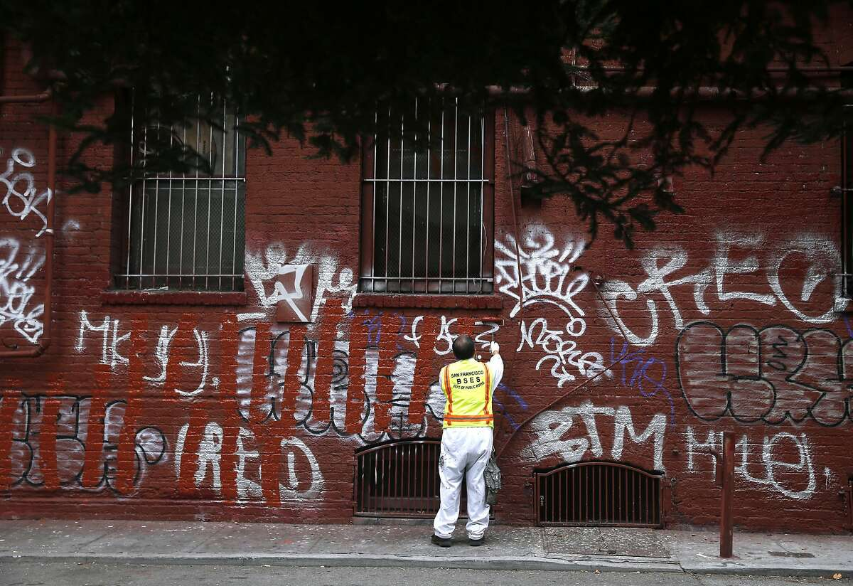 Yu Cheng of the Department of Public Works paints over graffiti covering a building in Chinatown's Quincy Alley, across from St. Mary's Square park, in San Francisco, Calif. on Friday, Aug. 21, 2015. The city attorney's office is suing a serial tagger known as Cozy Terry and is seeking more than $50,000 in damages for repeatedly defacing city property.