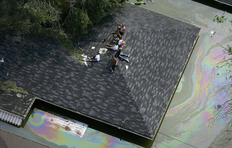 People are stranded on a roof by flooding from Hurricane Katrina in New Orleans as the levees begin to break and leak around Lake Ponchartrain. Photo: POOL, AFP/Getty Images / AFP; NGC