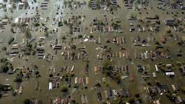 ** FILE ** Water surrounds homes just east of downtown New Orleans the day after Hurricane Katrina made landfall, in this Aug. 30, 2005 file photo.  Despite a flurry of promises, Congress repeatedly has put off  unpopular steps that experts say are necessary to fix the main flood insurance program. Hurricanes Katrina and Rita, back-to-back storms in 2005, shattered any notion the program was self-sustaining, threw the program roughly $20 billion into debt and called attention to its structural flaws.