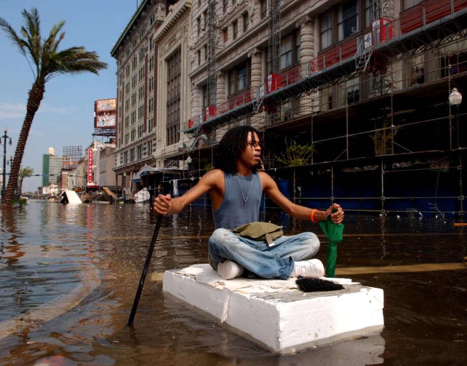 Jay Williams navigates his way down a flooded Canal Street on a piece of styrofoam. Photo: MATT ROURKE, AP / AUSTIN AMERICAN STATESMAN