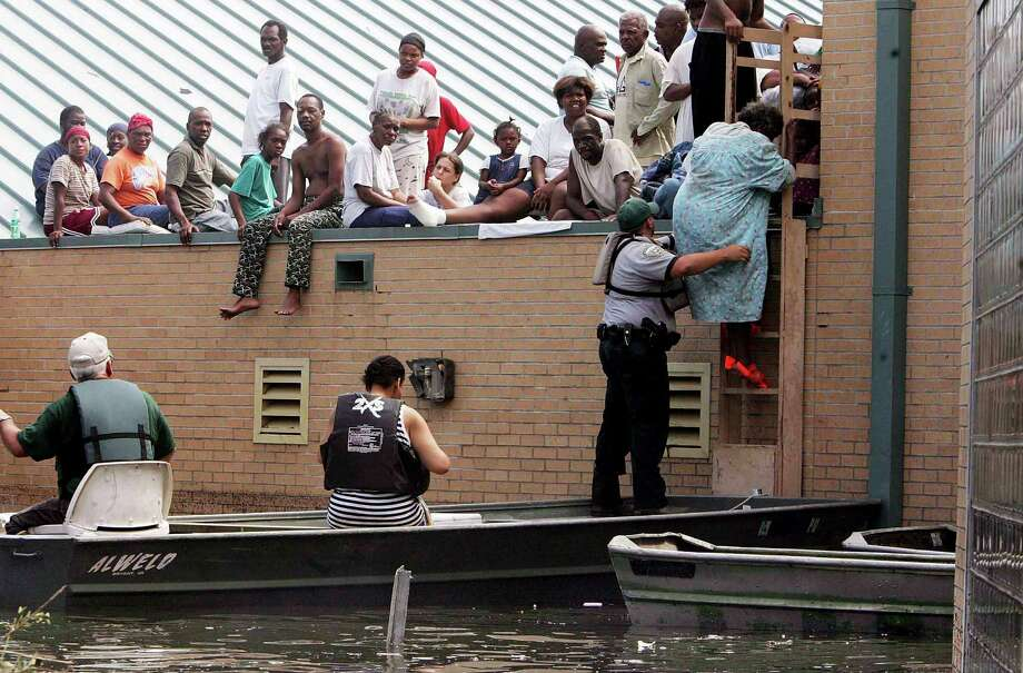 A woman is rescued from a school rooftop after being trapped with dozens of others in high water in Orleans parish during the aftermath of Hurricane Katrina in New Orleans. Photo: Mario Tama, Getty Images / Getty Images North America
