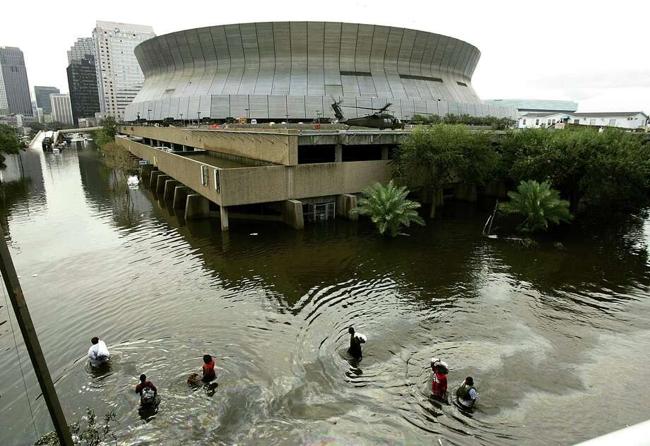 People walk through high water in front of the Superdomein New Orleans. Thousands of people are left homeless after Hurricane Katrina hit the area yesterday morning. Photo: Mark Wilson, Getty Images / Getty Images North America