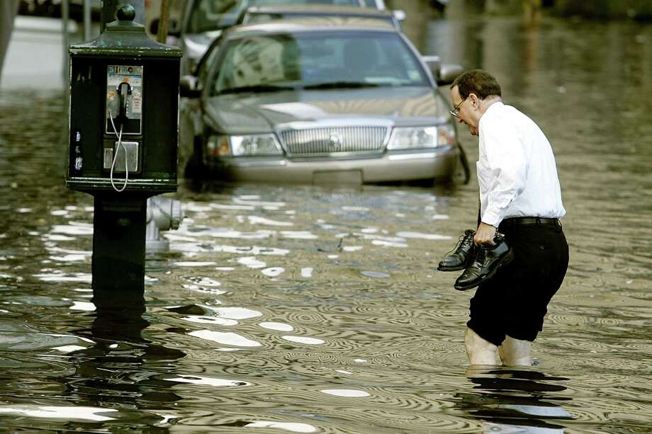 A man carries his shoes as he negotiates the high water on Canal Street in New Orleans. Photo: Mark Wilson, Getty Images / Getty Images North America