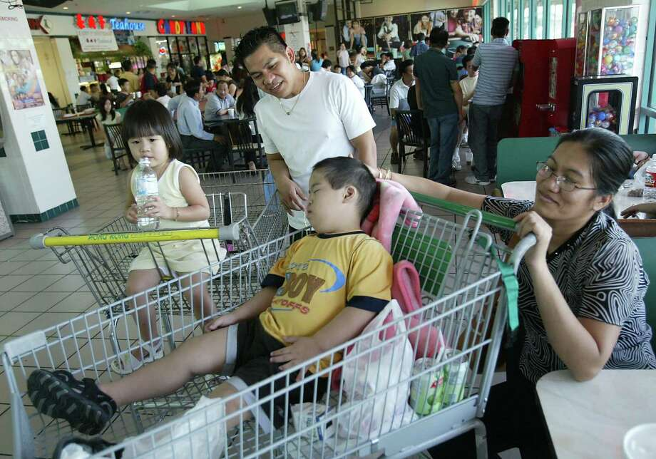 Vi Cao tries to keep her son Ricky comfortable inside Hong Kong City Mall. Photo: Mayra Beltran, Houston Chronicle / Houston Chronicle
