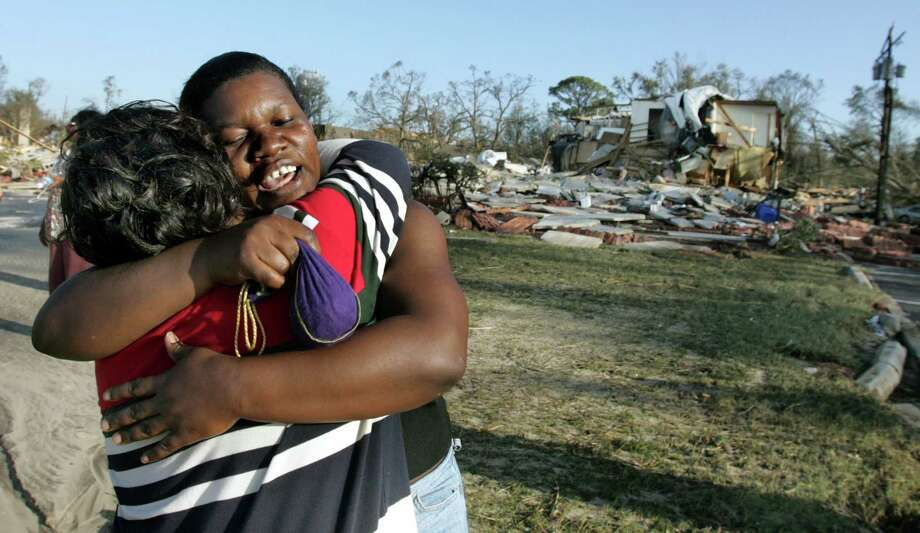 Roxona Park, left, gets a hug from Althea Brown as they meet at their apartment complex that was destroyed in Gulfport, Miss. Photo: LOUIS DELUCA, KRT / DALLAS MORNING NEWS