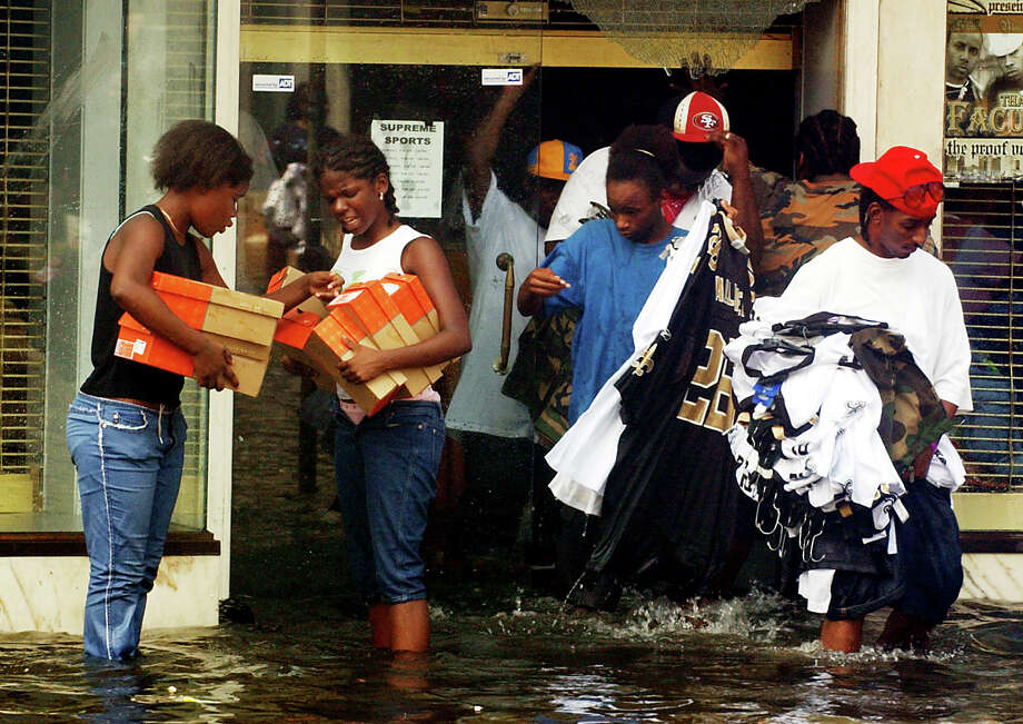 People remove goods from a store along Canal Street in New Orleans. Photo: MATT ROURKE, AP / AUSTIN AMERICAN STATESMAN