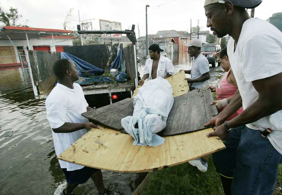 Friends and neighbors help Evelyn Turner, second from right,  load  the body of her common-law husband,  Xavier Bowie, onto a flatbed truck after he died in New Orleans. Xavier and Turner had decided to ride out Hurricane Katrina when they could not find away to leave the city. Xavier, who had lung cancer, died when he ran out of oxygen Tuesday afternoon. Photo: ERIC GAY, AP / AP