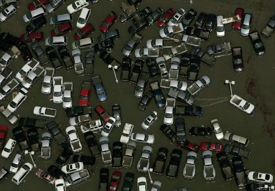 Vehicles are strewn about a dealership lot submerged in floodwaters in Slidell, La. Photo: SMILEY N. POOL, AP / THE DALLAS MORNING NEWS
