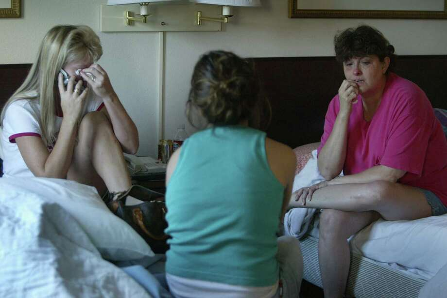 Brenda Watzke and sister-in-law Carol Dingeman weep while niece Heather Gillespie, 16, looks on as Brenda speaks to her husband in New Orleans. They learn of rioting and rising water inNew Orleans. Photo: Mayra Beltran, Houston Chronicle / Houston Chronicle