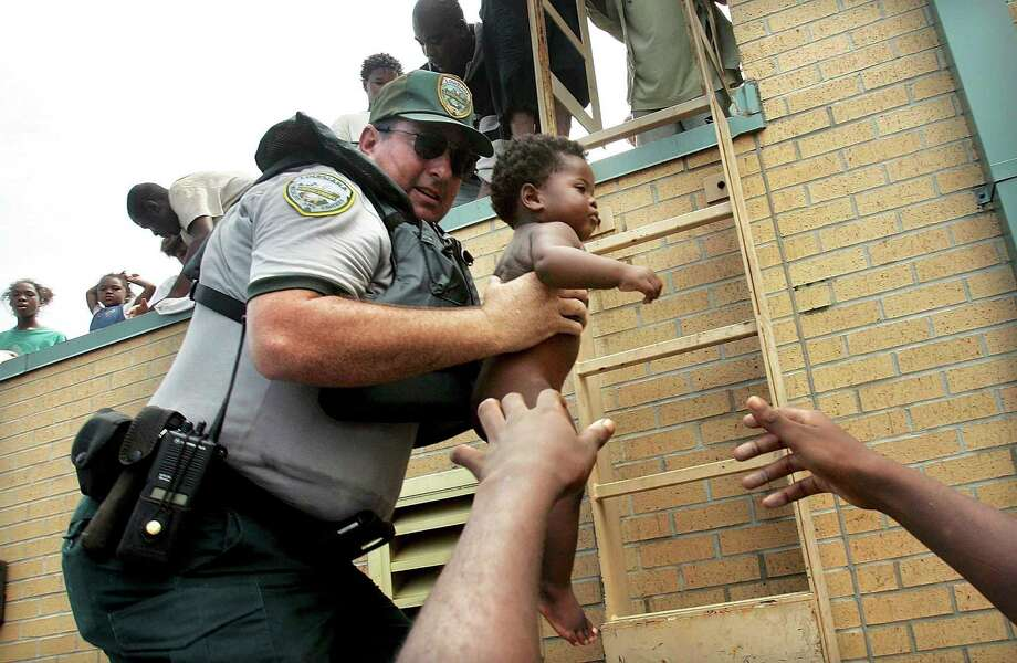 Mark Benton, of Louisiana Department of Wildlife and Fisheries, helps rescue 3-month-old Ishmael Sullivan from a school rooftop after he and his mother were trapped with dozens of others in high water in New Orleans Photo: Mario Tama, Getty Images / Getty Images North America