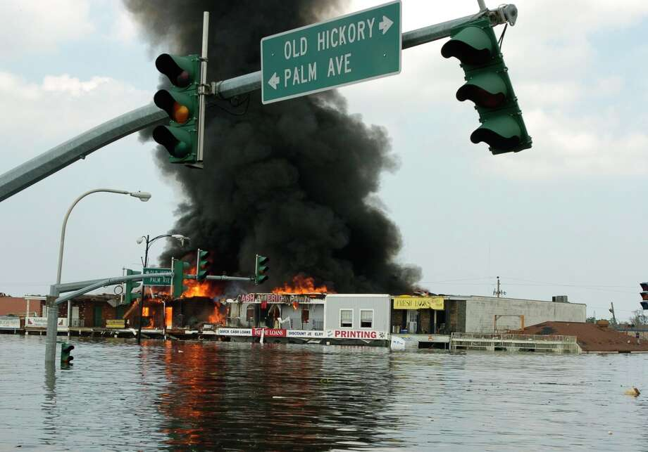 A shopping center burns despite being surrounded by floodwaters in Chalmette. Photo: MELISSA PHILLIP, HOUSTON CHRONICLE / HOUSTON CHRONICLE