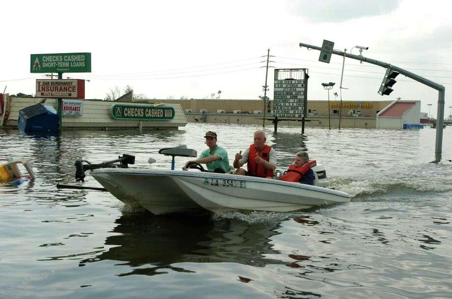 A boat navigates the flooded roadways  in Chalmette. Photo: MELISSA PHILLIP, HOUSTON CHRONICLE / HOUSTON CHRONICLE