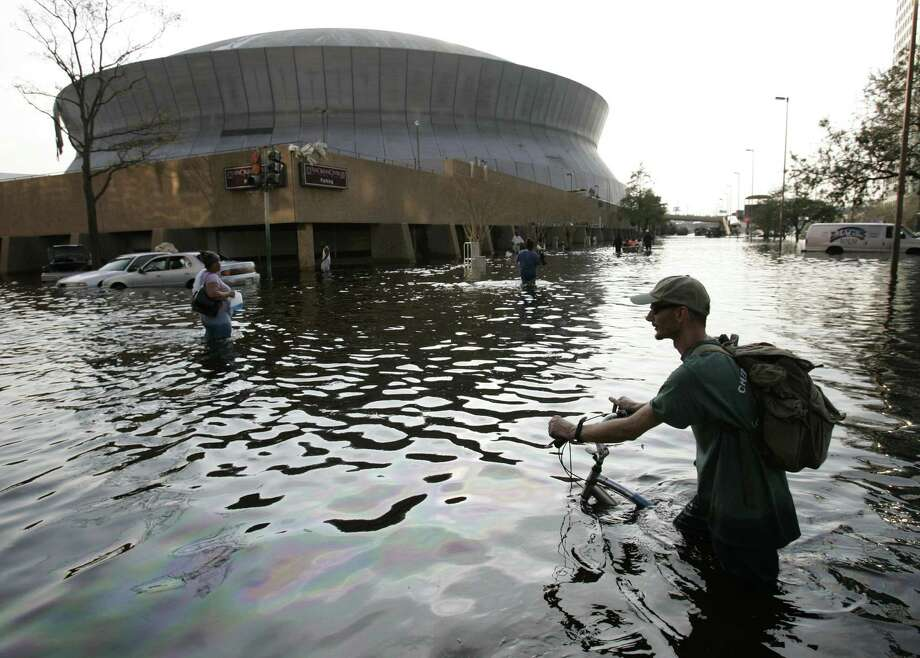A man pushes his bicycle through floodwaters near the Superdome in  New Orleans. Photo: ERIC GAY, AP / AP