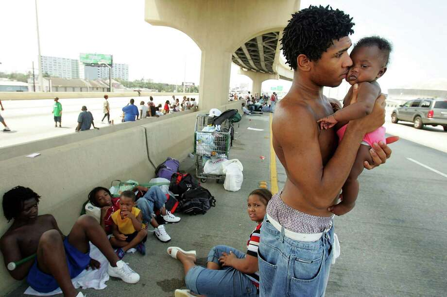 Daryl Thompson holds his 3-month-old daughter, Dejanae, as they wait with other displaced residents on a highway in the hopes of catching a ride out of New Orleans. Photo: Mario Tama, Getty Images / Getty Images North America