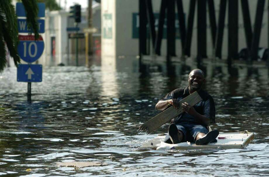 A man paddles toward the Superdome in New Orleans. Photo: MELISSA PHILLIP, HOUSTON CHRONICLE / HOUSTON CHRONICLE
