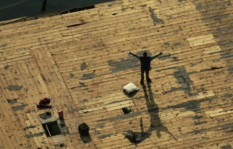 A person waits on a roof for rescue from floodwaters. Photo: SMILEY N. POOL, KRT / DALLAS MORNING NEWS
