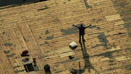 -- NO MAGS, NO SALES -- KRT US NEWS STORY SLUGGED: WEA-KATRINA KRT PHOTOGRAPH BY SMILEY N. POOL/DALLAS MORNING NEWS (August 31) NEW ORLEANS, LA -- A person waits on a roof for rescue from floodwaters in New Orleans, Louisiana, on Wednesday, August 31, 2005. (gsb) 2005