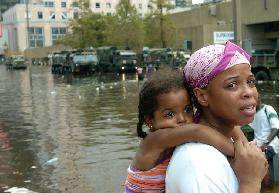 A woman who did not identify herself held a child as they reached the Superdome in New Orleans to take shelter from the aftermath of Hurricane Katrina.  Photo: MELISSA PHILLIP, HOUSTON CHRONICLE / HOUSTON CHRONICLE