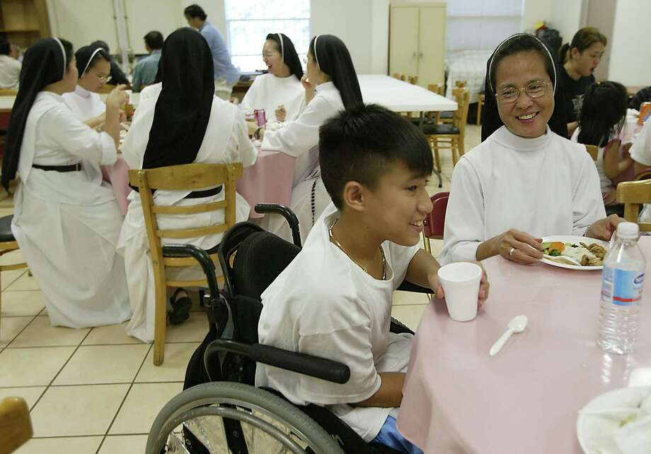 John Lam, left, 12, of East New Orleans, finishes dinner with sister Theresa Nguyen at the Vietnamese Dominican Sisters Convent where Vietnamese evacuees fleeing Hurricane Katrina found shelter in Houston. Photo: Mayra Beltran, Houston Chronicle / Houston Chronicle