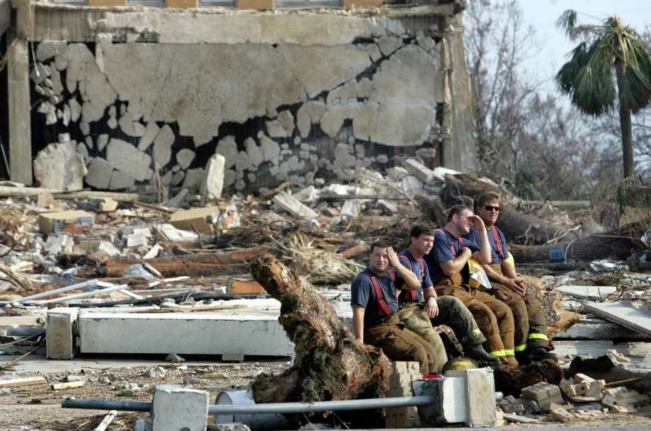 Four Biloxi firefighters try to rest as they wait for law enforcement search and rescue personnel to look for survivors at a hotel property near Highway 90 in Biloxi, Miss. Photo: LOUIS DELUCA, AP / THE DALLAS MORNING NEWS