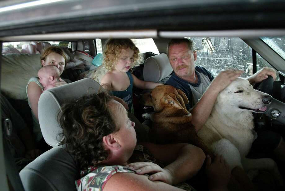 With nowhere else to go since their home was destroyed by Hurricane Katrina, the Stump family had been staying it their car in Biloxi, Miss. From right, clockwise, Bob Stump and his wife, Nina, their daughter, Beth (backseat), tended to her 9-week-old daughter, Breanna, as her other daughter, Bonnie, 2, plays with one of the family's two dogs.  Photo: JARED LAZARUS, KRT / MIAMI HERALD